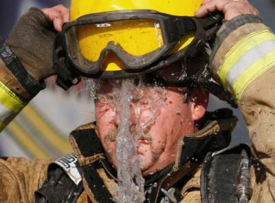 Пожарный обливает себя водой