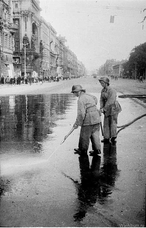 Пожарные смывают с асфальта на Невском проспекте кровь ленинградцев, убитых в результате немецкого артобстрела (1943 год)
